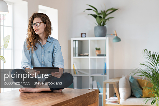 Beautiful smiling woman with digital tablet sitting cross legged on table at home - p300m2277559 by Steve Brookland