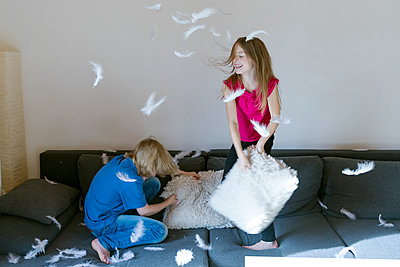 Pillow fight between brother and sister at home - p300m1206294 by Sandra Roesch