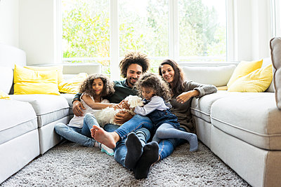 Happy family with dog sitting together in cozy living room - p300m1535093 by Robijn Page