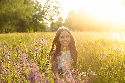 Portrait of smiling girl crouching on flower meadow at evening twilight - p300m1587981 von Sandra Roesch