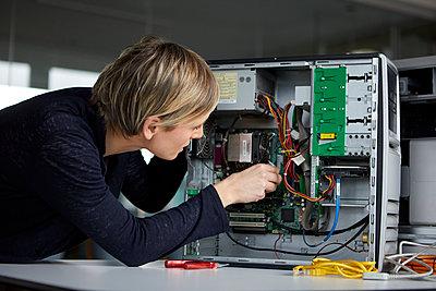 Woman assembling desktop pc in office - p300m2180573 by Rainer Berg