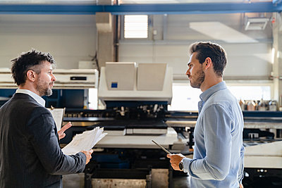 Businessman with paper discussing with colleague while standing at factory - p300m2225143 by Daniel Ingold