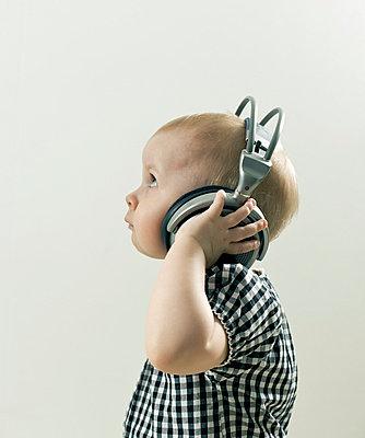 Toddler with headphones - p3882631 by Johannes Romppanen