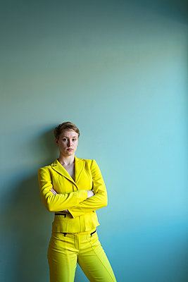 Young woman wearing yellow pantsuit - p427m2109256 by Ralf Mohr