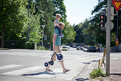 Father shoulder carrying toddler son over pedestrian crossing - p429m943246f by Tiina & Geir