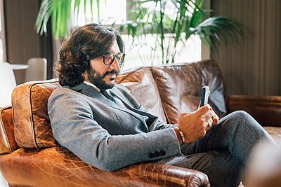 Italy, Businessman with smart phone sitting on sofa in creative studio - p924m2300731 by Eugenio Marongiu