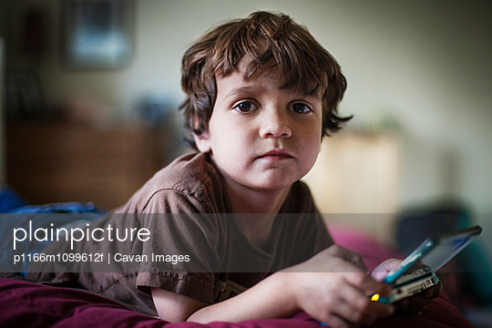 Portrait of boy holding handheld gaming device while lying on bed at home - p1166m1099612f by Cavan Images