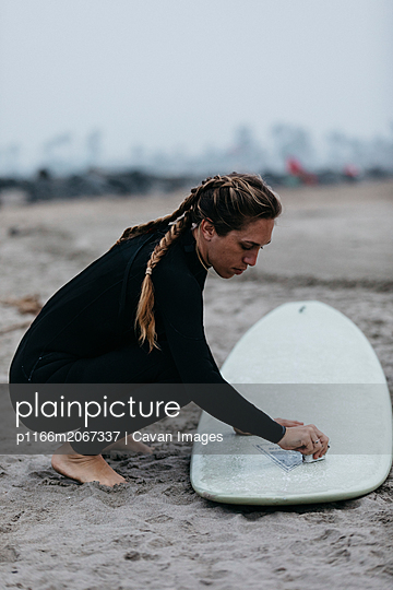 Side view of woman polishing surfboard while crouching on sand at beach against sky - p1166m2067337 by Cavan Images