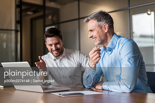 Smiling male professionals discussing over laptop in board room - p300m2274148 by Daniel Ingold