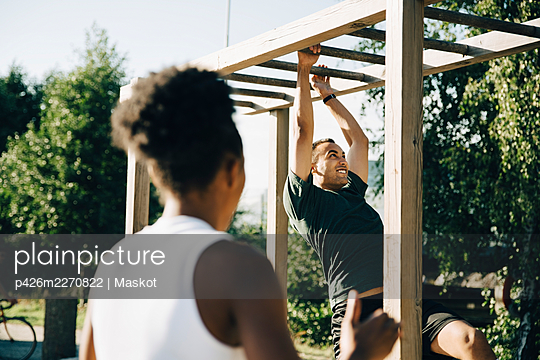 Male athlete hanging on monkey bar while sportswoman looking at him in park on sunny day - p426m2270822 by Maskot
