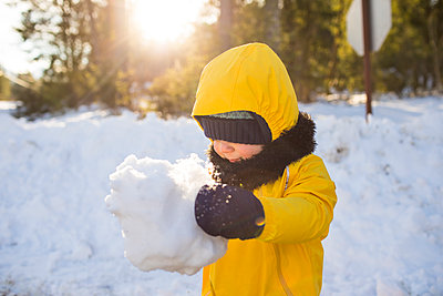 Toddler boy holds giant snowball. - p1166m2093911 by Cavan Images