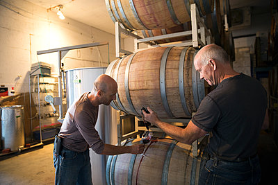 Vintners checking and tasting red wine in winery barrel room - p1192m1183798 by Hero Images