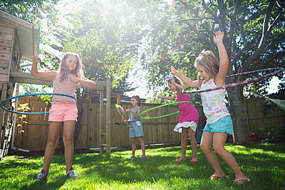 Girls spinning in plastic hoops in sunny backyard - p1192m1183936 by Hero Images