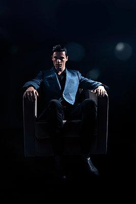 Man in blazer sitting on armchair - p1248m2206136 by miguel sobreira