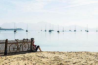 Cyclist on the beach, Port de Pollenca, Majorca, Balearic Islands, Spain - p1316m1422606 by Daniel Schoenen