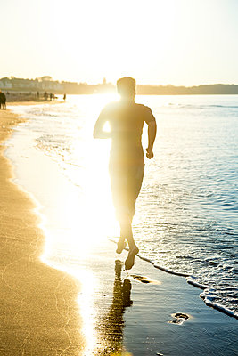 Man jogging at the beach at sunset - p300m2081329 von pure.passion.photography