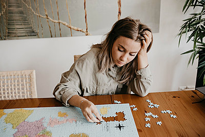 Confused woman playing with jigsaw puzzle at table during home quarantine - p300m2189238 by letizia haessig photography