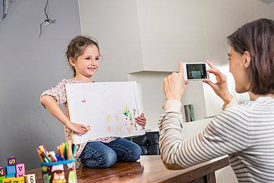 Mother taking photo of girl with painting through mobile phone at home - p300m2287288 by Stefanie Aumiller