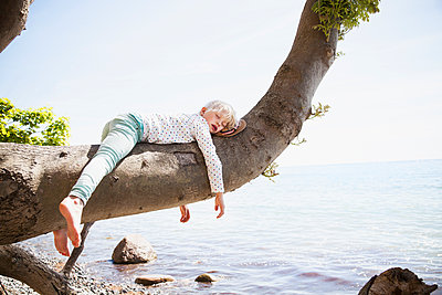 Young girl sleeping on branch by sea - p312m1121644f by Lina Karna Kippel