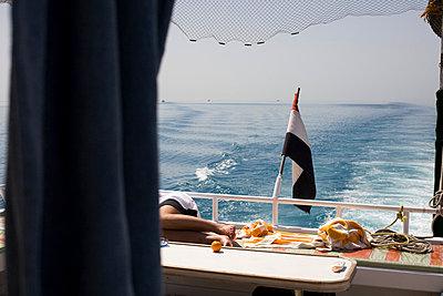 Man sleeping on sun deck of boat - p3881737 by Ulrike Leyens