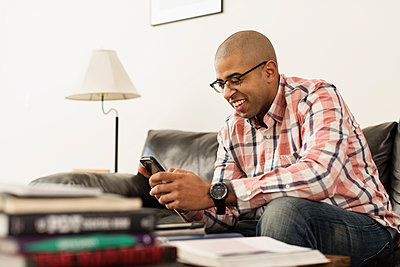 Mixed race soldier texting with cell phone on sofa - p555m1412425 by Roberto Westbrook