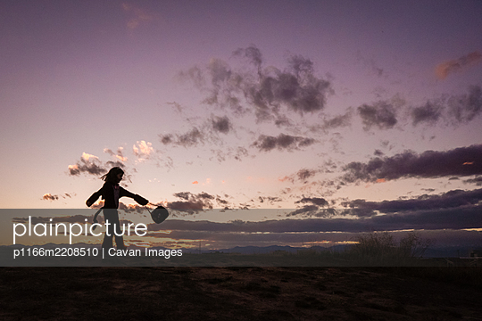 A young girl a twirls a halloween bucket on top of a hill at sunset - p1166m2208510 by Cavan Images