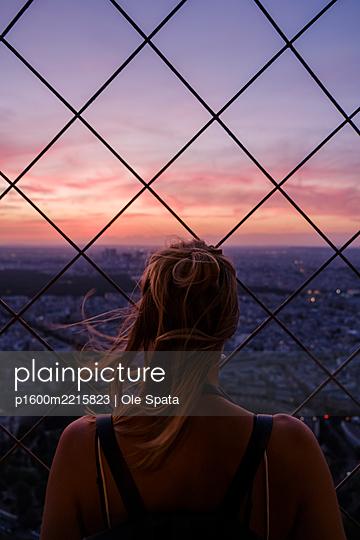 Junge Frau blickt vom Eiffelturm auf Paris - p1600m2215823 von Ole Spata