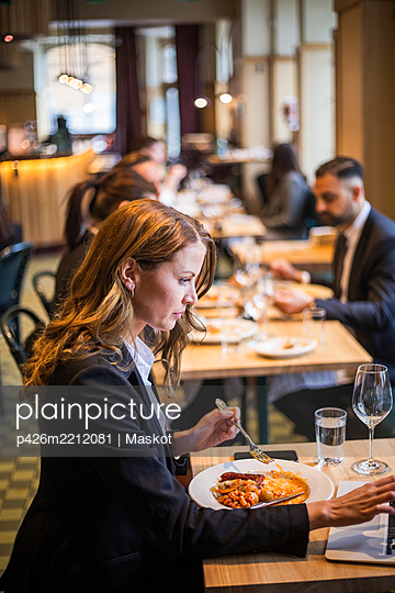 Side view of female business person using laptop in restaurant - p426m2212081 by Maskot