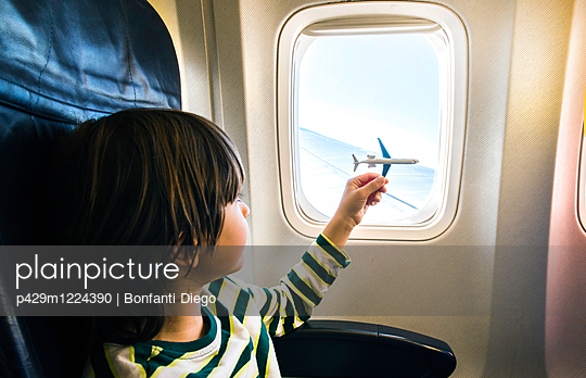 Boy playing with toy airplane at airplane window - p429m1224390 by Bonfanti Diego