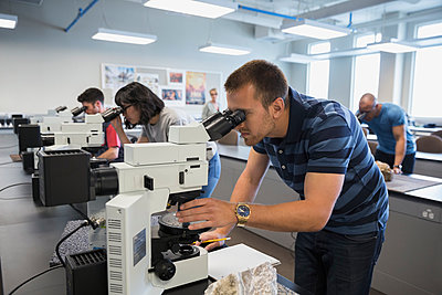 College science students using microscopes in classroom - p1192m1036744f by Hero Images
