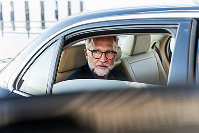 Mature businessman sitting on backseat in car, looking out of window - p300m2023969 von Uwe Umstätter