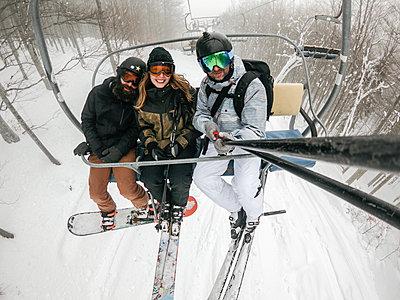 Italy, Modena, Cimone, portrait of happy friends taking a selfie in a ski lift - p300m2029474 von Juri Pozzi