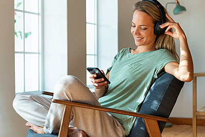 Smiling woman at home with headphones in comfortable loungewear sitting in armchair listening to music looking at smartphone - p300m2276391 von Steve Brookland