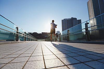 Young Caucasian man running in metropolitan area - p307m1101678f by Yosuke Tanaka