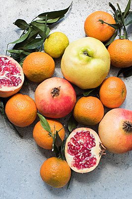 Overhead view of colourful fruits and halved pomegranate - p429m1103120 by Magdalena Niemczyk - ElanArt