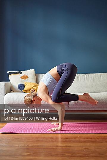 Junge Frau macht eine Yoga Übung - p1124m1589403 von Willing-Holtz