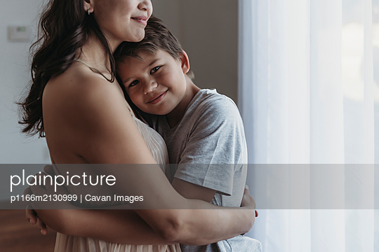 School-aged son being embraced by mother in natural light studio - p1166m2130999 by Cavan Images