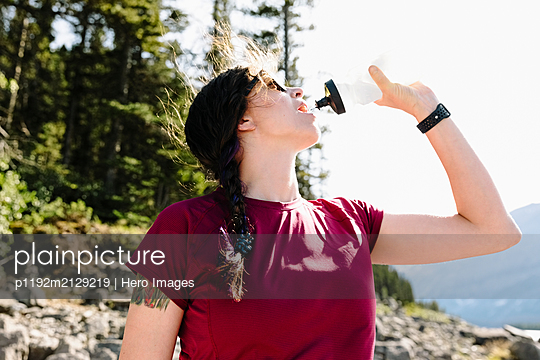 Female hiker drinking water - p1192m2129219 by Hero Images