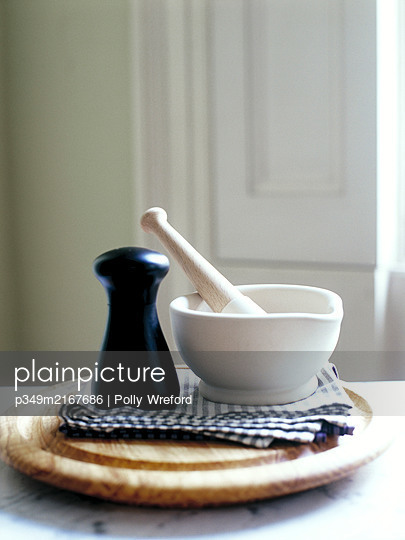 Mortar and pestle and pepperpot on chopping board - p349m2167686 by Polly Wreford
