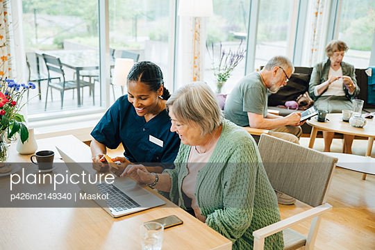 Smiling female healthcare worker assisting senior woman doing online shopping with credit card and laptop in nursing hom - p426m2149340 by Maskot