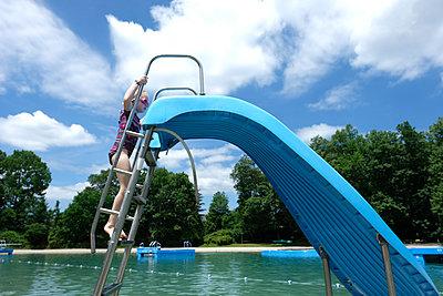 Side view of girl climbing steps of water slide in resort against cloudy sky - p1166m1489632 by Cavan Images