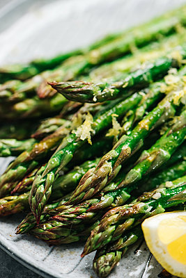 Closeup of lemon garlic asparagus tips - p1166m2162856 by Cavan Images