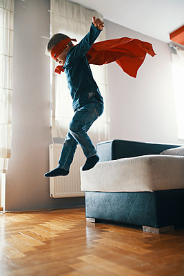 Little boy dressed up as a superhero playing at home - p300m1581539 by Zeljko Dangubic
