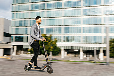 Casual young businessman riding electric scooter in the city - p300m2160627 by Josep Rovirosa