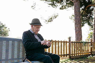 Old man with, sitting on bench, using smartphone - p300m2166548 by Josep Rovirosa