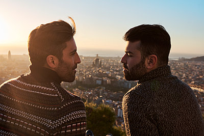 Romantic gay couple looking at each other with cityscape in background, Bunkers del Carmel, Barcelona, Spain - p300m2257343 by Veam