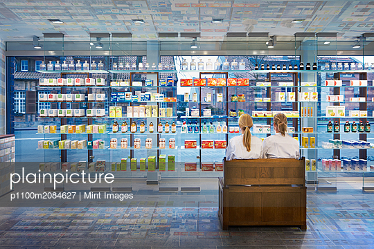 Pharmacists sitting in modern pharmacy,Altenberge, Altenberge, Germany - p1100m2084627 by Mint Images