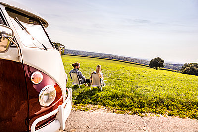 Couple sitting on camping chairs next to van in rural landscape - p300m2041846 by Jo Kirchherr