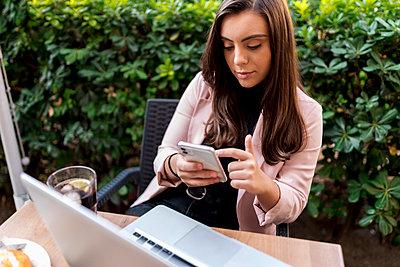 Young female entrepreneur using smart phone while sitting on terrace of cafe - p300m2221335 by Ezequiel Giménez