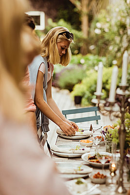 Teenage girl arranging plate on table for dinner party - p426m2238252 by Maskot